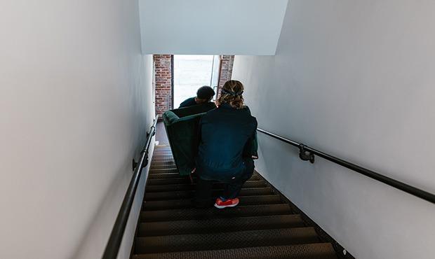 due ragazzi trasportano un divano per le scale